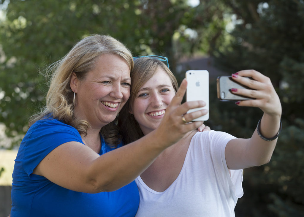 1307-07 75.JPG Syd and Brooke Jacques take photos of themselves on their smart phones. Sarah Coyne research that Teens feel closer to parents when they connect on social media. July 3, 2013 Photography by Mark A. Philbrick/BYU Copyright BYU Photo 2013 All Rights Reserved photo@byu.edu (801)422-7322